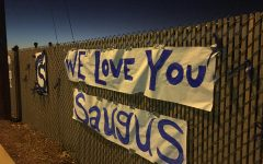 These posters, along with hundreds of blue and white glow sticks, lined the fences along the street from Saugus High School all the way to Central Park on the night of the vigil.