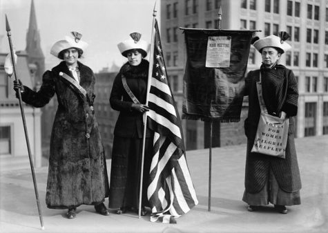 """Photo shows women suffrage hikers General Rosalie Jones, Jessie Stubbs, and Colonel Ida Craft, who is wearing a bag labeled """"Votes for Women pilgrim leaflets"""" and carrying a banner with a notice for a """"Woman Suffrage Party. Mass meeting. Opera House. Brooklyn Academy of Music. January 9th at 8:15 p.m."""""""