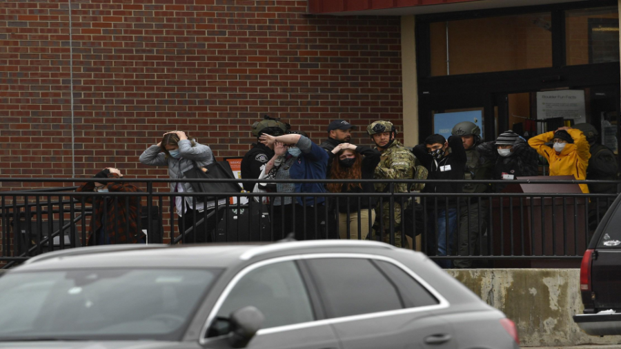Law enforcement personnel escort people who were inside the King Soopers grocery store in south Boulder out after the mass shooting that left 10 dead on March 22, 2021.