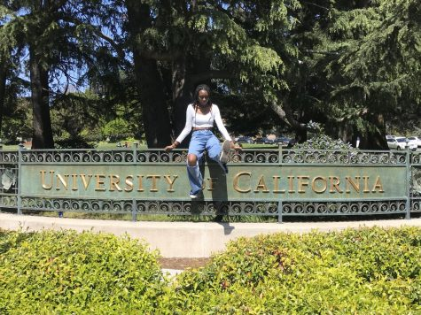 A candid moment of graduating senior, Zara Koroma, sitting on the gate outside UC Berkeley