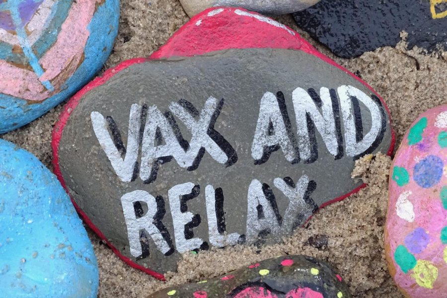 Painted rocks in the sand, one reads