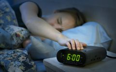 Young woman pressing snooze button on early morning digital alarm clock radio.