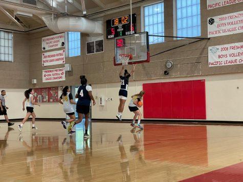 Josie Regez (10) jump stopping under the basket before scoring.